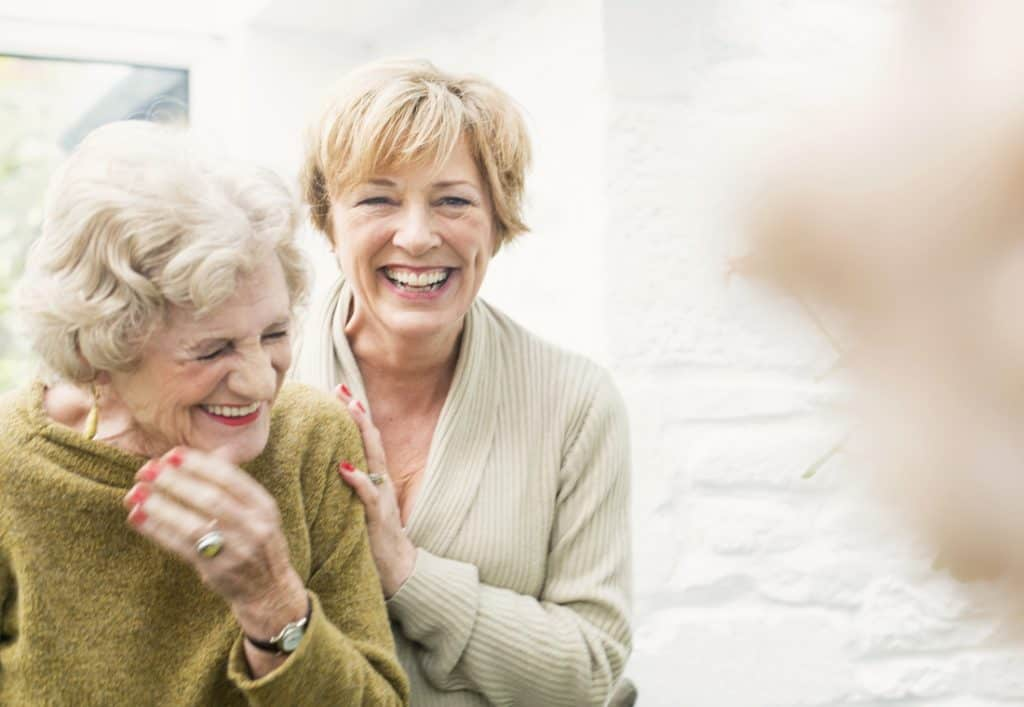 two mature women having a laugh together